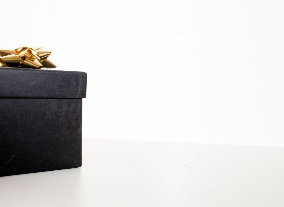 Musta lahjapaketti, jossa kultainen russetti päällä